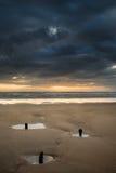 Ajardine com os quebra-mar velhos que projetam-se da areia na baía de Rhosilli Foto de Stock Royalty Free