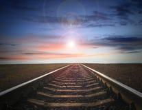 Ajardine com os trilhos que partem a nivelar o céu com sol Imagens de Stock