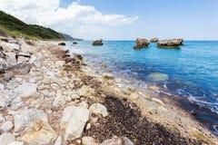 Ajardine com pedregulhos e rochas na costa com mar azul Fotos de Stock Royalty Free
