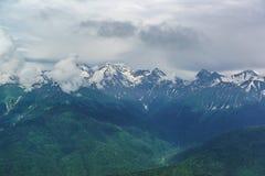 Ajardine com picos nevado altos das montanhas de Cáucaso Nuvens que escondem as partes superiores Imagens de Stock Royalty Free