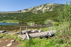 Ajardine com a ponte de madeira sobre o rio na montanha de Pirin, no lago Bezbog e no pico Imagem de Stock Royalty Free