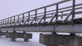 Ajardine com a ponte longa de madeira velha no gelo nevado do lago e na névoa da manhã video estoque