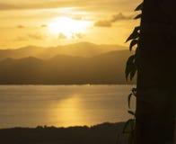Ajardine com por do sol no litoral sobre a cordilheira Fotos de Stock Royalty Free