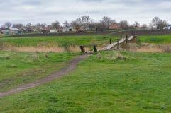 Ajardine com prado e o passadiço velho sobre o rio pequeno Foto de Stock