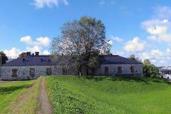 Ajardine com prado verde, trajeto e a casa de pedra Imagem de Stock