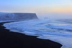 Ajardine com a praia da areia preta e as pilhas do mar no fundo Fotos de Stock Royalty Free