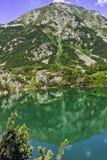Ajardine com reflexão do pico de Hvoynati no lago Okoto, montanha de Pirin Imagens de Stock