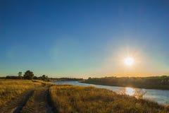 Ajardine com rio e estrada de terra ao tempo do por do sol Imagem de Stock Royalty Free