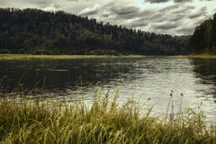 Ajardine com rio, montanhas e floresta em uma costa Céu com as nuvens de tempestade sobre o rio Fotos de Stock Royalty Free