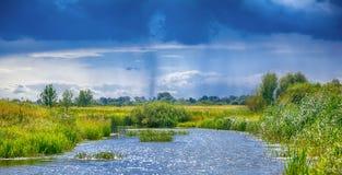 Ajardine com rio, nuvens e chuva no céu Fotografia de Stock