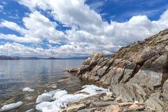 Ajardine com rocha textured, as nuvens brancas e gelo de derretimento no sp Fotografia de Stock
