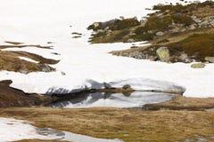 Ajardine com rochas e neve em um dia ensolarado Fotografia de Stock