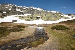 Ajardine com rochas e neve em um dia ensolarado Fotos de Stock