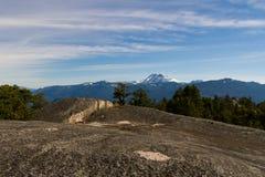 Ajardine com rochas, floresta e as montanhas cobertos de neve Imagens de Stock Royalty Free