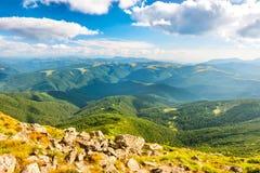 Ajardine com rochas, os montes verdes e as nuvens brancas Foto de Stock