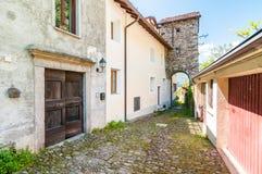 Ajardine com a rua estreita com as paredes de pedra do Maccagno, Itália Imagem de Stock