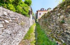 Ajardine com a rua estreita com as paredes de pedra do Maccagno, Itália Imagens de Stock