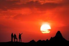Ajardine com a silhueta de povos eretos e do céu bonito Fotografia de Stock Royalty Free