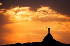 Ajardine com silhueta de um homem no pico de montanha Foto de Stock