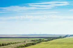 Ajardine com terra agrícola e facilidades industriais no horizonte Imagem de Stock