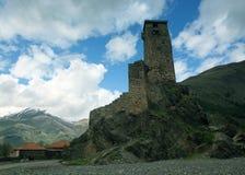 Ajardine, com a torre de protetor de Svan em um fundo de picos e de nuvens neve-tampados de montanha, Svaneti Imagens de Stock Royalty Free