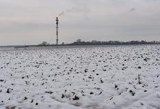 Ajardine com a tubulação de gás ardente do poço petrolífero em um campo agrícola na estação do inverno Fotos de Stock