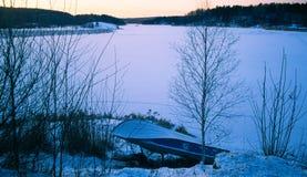 Ajardine com um barco em um lago congelado Manhã Imagem de Stock Royalty Free