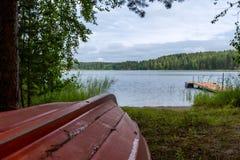 Ajardine com um barco vermelho na costa de como Imagens de Stock