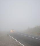 Ajardine com um carro na estrada na névoa com incluir dos faróis Fotografia de Stock