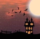 Ajardine com um castelo de Dia das Bruxas e uma lua grande Foto de Stock Royalty Free