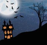 Ajardine com um castelo de Dia das Bruxas e uma lua grande Fotos de Stock