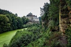 Ajardine com um castelo velho e as rochas do arenito Imagem de Stock