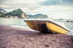Ajardine com um catamarã na praia em Petrovac Imagens de Stock