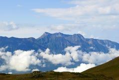 Ajardine com um cume azul e as nuvens no vale profundamente para baixo Imagem de Stock Royalty Free