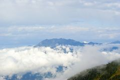 Ajardine com um cume azul e as nuvens no vale profundamente para baixo Fotografia de Stock