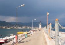 Ajardine com um farol na cidade do porto de Alanya no alvorecer Fotos de Stock