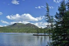 Ajardine com um lago e as montanhas ao longo dos bancos. Imagens de Stock Royalty Free
