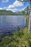 Ajardine com um lago e as montanhas ao longo dos bancos. Fotografia de Stock