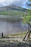 Ajardine com um lago e as montanhas ao longo dos bancos. Imagem de Stock Royalty Free