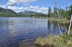 Ajardine com um lago e as montanhas ao longo dos bancos. Fotografia de Stock Royalty Free