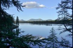 Ajardine com um lago e as montanhas ao longo dos bancos Imagens de Stock