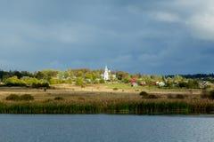 Ajardine com um lago e uma igreja e uma vila Imagens de Stock