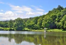 Ajardine com um lago em um dia de verão Imagens de Stock