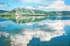 Ajardine com um lago, montanhas, reflexão das nuvens na água Imagens de Stock