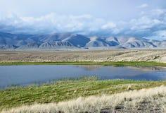 Ajardine com um lago pequeno em um vale das montanhas Fotografia de Stock Royalty Free