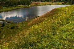 Ajardine com um monte, um rio e uma reflexão das nuvens Foto de Stock