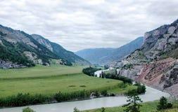 Ajardine com um rio que flui entre as montanhas Imagem de Stock Royalty Free