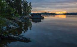 Ajardine com uma casa no lago em Carélia Fotografia de Stock Royalty Free