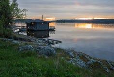 Ajardine com uma casa no lago em Carélia no por do sol Imagem de Stock