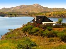 Ajardine com uma casa pequena, um lago, um arbusto, umas árvores da acácia do espinho do camelo e umas montanhas em Namíbia centr Imagens de Stock Royalty Free